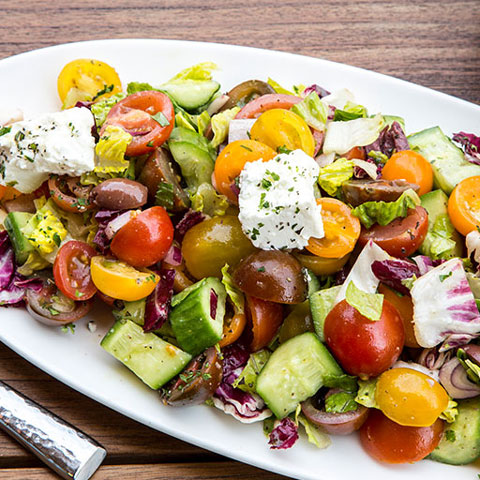 Greek salad with feta cheese, olives and tomatoes.