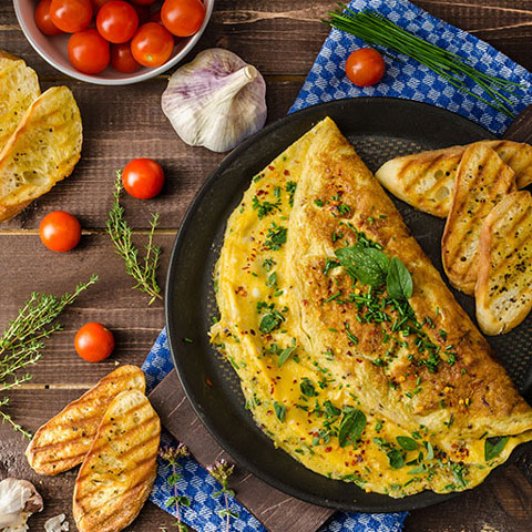 Omelet image from above with bread and tomatoes.