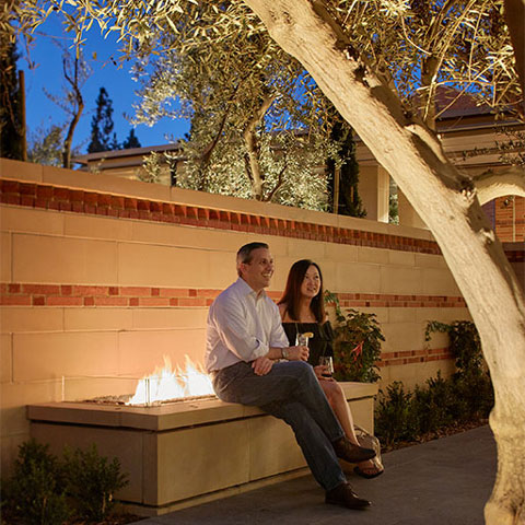 Two guests enjoying a drink at night on the outdoor patio near the outdoor fireplace.